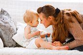 Cute bebê com chupeta e jovem mãe jogando no divã