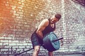 Athletic Man Working Out With A Barbell In Front Of Brick Wall. Strength And Motivation. Outdoor Wor poster