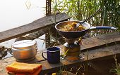 Camping Food Making. Pasta On Pan On Tourist Fire Stove. Camp Cooking On The Shore Of The Lake. poster