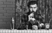 Barman With Beard And Surprised Face Drinks Out Of Glass With Drinking Straw Cocktail. Man Drinks Co poster