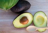 Avocado And Avocado Pieces On A Wooden Floor And Has A Background Of Green Tree, Selected Focus poster