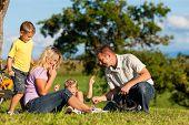 Glückliche Familie (Vater, Mutter und zwei Söhne) auf Übernachtung mit Fahrrädern - haben sie eine Pause