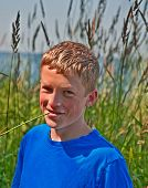 stock photo of 13 year old  - This cute Caucasian 13 year old boy is outdoors with a stem of long grass in his mouth as he is smiling through his braces - JPG
