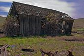 Old Barn With Antique Equipment In Foreground