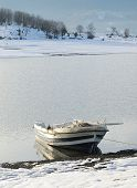 Boat In The Lake And Snow On The Beach
