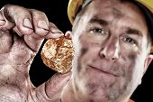 pic of gold mine  - A gold miner shows a golden nugget freshly excavated from a mine - JPG