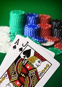 Player showing Black Jack against a big stack of chips blurred in the background.