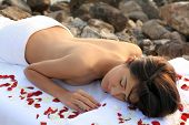 Beautiful woman getting massage & spa treatment in natural setting.