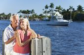 Happy senior man and woman couple together by a river or sea in a tropical location with a boat sail
