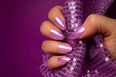 Female Hand With Shiny Purple Nails Is Holding Purple Glittered Fabric On Purple Background, Nail Ca poster