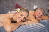 Senior man and beautiful woman lying down on massage beds at spa. Mature couple lying on massage tab poster