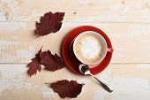 Autumn Coziness Concept. Warm And Cozy Autumn Coffee Time. Red Ceramic Tableware With Tasty Beverage poster