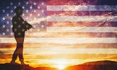 Armed soldier with rifle standing and looking on horizon. USA flag. Silhouette at sunset. War, army, poster
