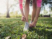 Close Up Of Young Woman Lace Up Her Shoe Ready To Workout On Exercising In The Park With Warm Light  poster
