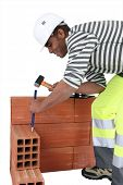 Bricklayer using a hammer and chisel