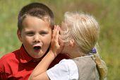 Girl whispering secret to a stunned boy