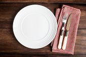 Empty White Plate, Fork And Knife On A Checkered Red Napkin On An Old Wooden Brown Background, Top V poster