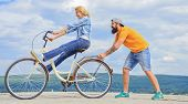 Woman Rides Bicycle Sky Background. Girl Cycling While Man Support Her. Man Helps Keep Balance Ride  poster