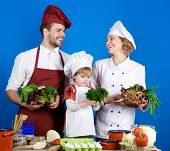 Child With Parents Cooking At Kitchen Table. Happy Loving Family Preparing Dinner Together. Cheerful poster