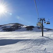 Chair-lift And Blue Sky With Sun And Sunbeams. Greater Caucasus In Winter, Mount Shahdagh, Azerbaija poster