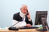 Photo of a mature businessman with injuries talking on the phone whilst trying to work on his comput