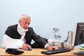 Photo of a mature businessman with multiple injuries sitting at his desk struggling to work on his c