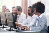 Young Customer Service Executives Using Earphones Working In Call Center poster