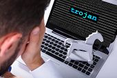 Businessman With Laptop Screen Showing Trojan Text With Binary Digits poster