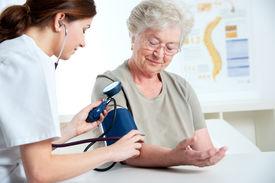pic of medical assistant  - Female doctor measuring blood pressure of senior woman - JPG