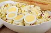 stock photo of boil  - Serving bowl of potato salad with sliced hard boiled egg - JPG
