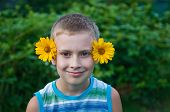 Cute Boy With Flowers On Ears Having Fun