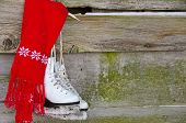 stock photo of red siding  - Bright red scarf with ice skates hanging on barn siding.