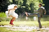 foto of white gown  - bride and groom splashing water in the nature trash the dress - JPG