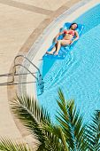 Young woman in red swimsuit bakes lying on inflatable mattress on water near to edge of pool