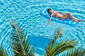 Frau im roten Badeanzug sunbathes auf aufblasbare Matratze im pool
