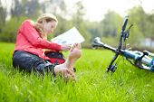 Girl Cyclist On A Halt Reads Lying In Fresh Green Grass Barefoot