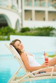 Happy Young Woman With Cocktail Enjoying Laying On Chaise-longue