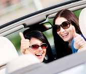 stock photo of turn-up  - Two happy girls sitting in the car and thumbing up turn back and have fun while having little car trip - JPG