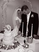 stock photo of cleaving  - BW photo of Bride and Groom cutting cake at a traditional wedding - JPG