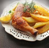 roasted chicken leg with fried potato and lemon