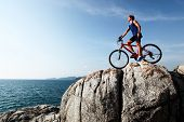 Young athlete standing on top of a mountain with bicycle and enjoying valley view