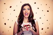 Thrilled beautiful brunette holding cup of coffee while coffee beans falling around her, with beige