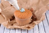Confectioner decorating tasty cupcake with butter cream, on color wooden background