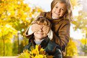 picture of guess  - Portrait of little blond girl hide boys eye with guess who surprise in autumn park - JPG