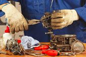 Serviceman repairing old car engine carburetor