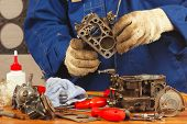 stock photo of carburetor  - Mechanic repairing the old car engine carburetor - JPG