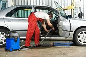 Automobile cleaning theme. Mechanic hoovering the car cabin with vacuum cleaner at auto repair shop