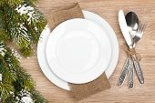 Empty plate, silverware set and christmas tree on wooden table