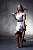 Young woman bodybuilder with hammer and axe. White colors.