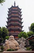 Smiling Buddha Statue In Front Of A Distorted Ruigang Pagodda, Suzhou, China
